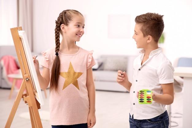 家で絵を描いている兄弟と少女 Premium写真