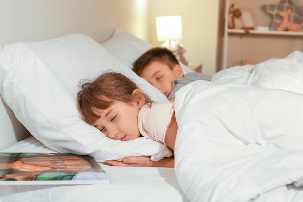 Маленькая девочка с братом, спящим в постели ночью