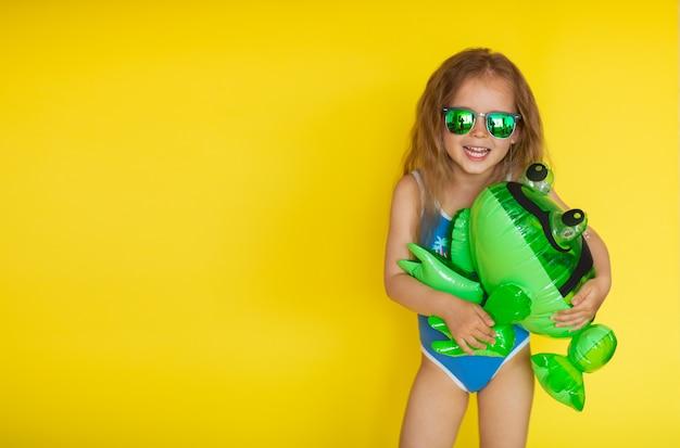 Маленькая девочка с каштановыми волосами в синем купальнике позирует на желтом фоне