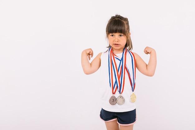 갈색 머리에 스포츠 챔피언 메달이 목에 달린 어린 소녀가 힘의 상징을 만들고 있습니다. 스포츠와 승리 개념