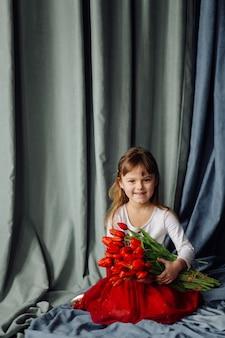 빨간 튤립의 무리와 함께 어린 소녀