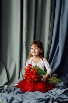 Little girl with bunch of red tulips