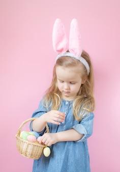 다채로운 부활절 달걀의 전체 나무 바구니와 서 토끼 귀를 가진 어린 소녀