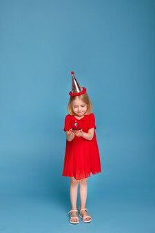 파란색 표면에 그녀의 생일에 케이크와 함께 어린 소녀