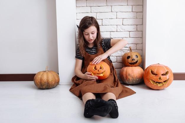 집에서 할로윈에 호박을 조각한 어린 소녀가 거실의 벽난로 옆에 앉아 있습니다. 트릭 또는 치료. 할로윈을 축하하는 아이.