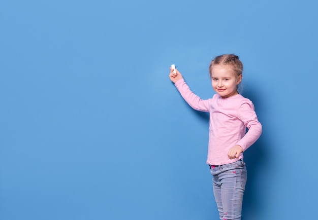 Little girl with chalk on blue background