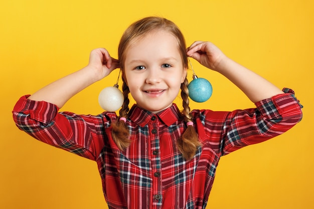 Little girl with christmas ball toys near the ears.