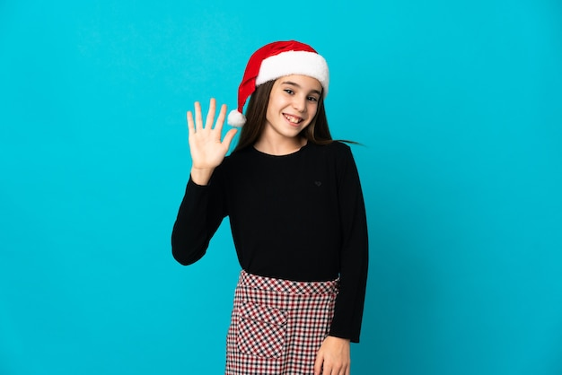 Little girl with christmas hat isolated on blue background saluting with hand with happy expression