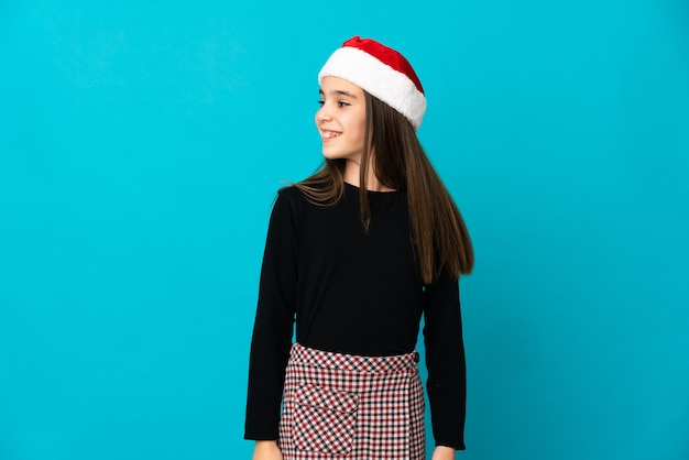 Little girl with christmas hat isolated looking to the side and smiling