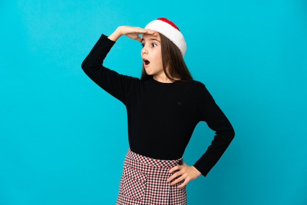 Маленькая девочка в новогодней шапке на синем фоне делает неожиданный жест, глядя в сторону