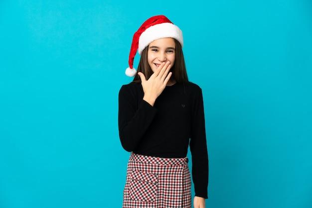 青い背景に分離されたクリスマスの帽子を持つ少女幸せと笑顔の手で口を覆う