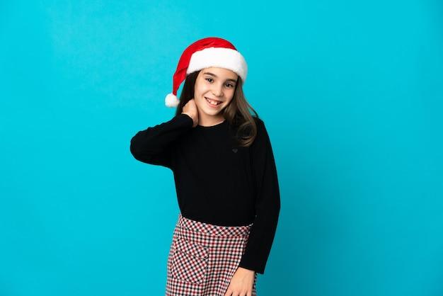 笑って青い背景で隔離のクリスマス帽子を持つ少女