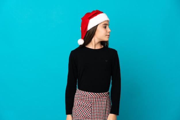 측면을 찾고 파란색 배경에 고립 된 크리스마스 모자와 어린 소녀