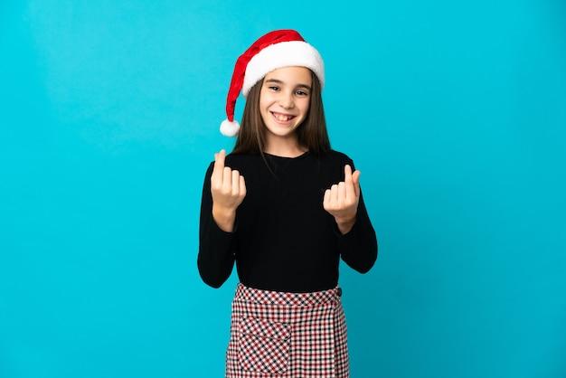 お金のジェスチャーを作る青色の背景に分離されたクリスマス帽子を持つ少女