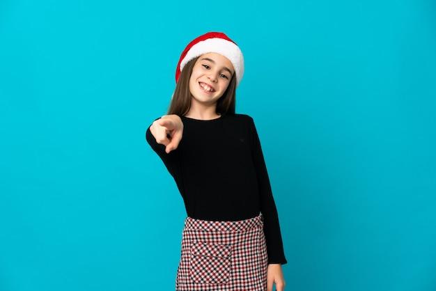 幸せな表情で正面を指している青い背景に分離されたクリスマス帽子を持つ少女