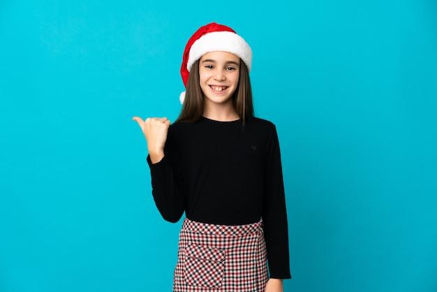 製品を提示する側を指している青い背景で隔離のクリスマス帽子を持つ少女