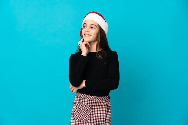 見上げながらアイデアを考えて青い背景で隔離のクリスマス帽子を持つ少女