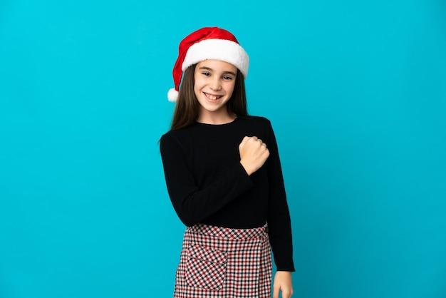 Маленькая девочка в новогодней шапке изолирована на синей стене празднует победу