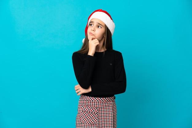 Маленькая девочка в рождественской шапке изолирована на синей стене, сомневаясь