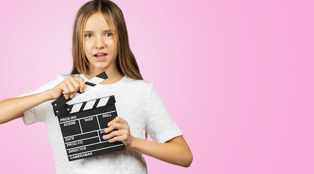 Little girl with a clapper board isolated