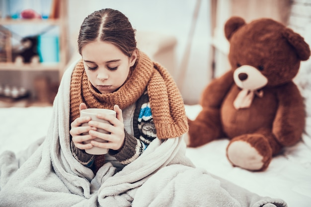 Little girl with cold in scarf and blanket with hot beverage