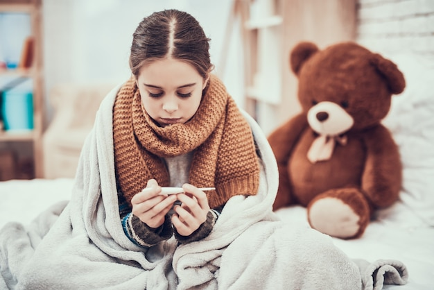 Little girl with cold in scarf and blanket with thermometer.