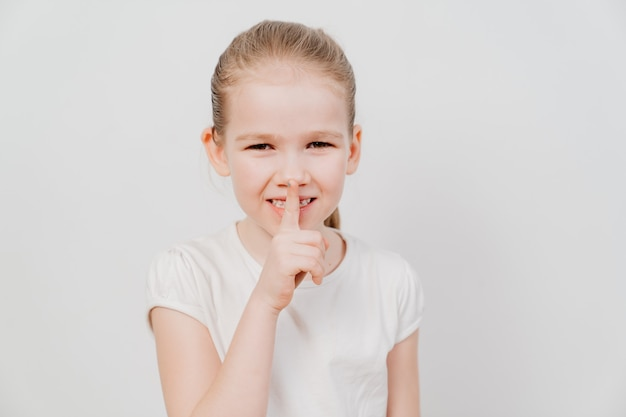 A little girl with collected hair in a white t-shirt stands on a white surface, holds his index finger in front of his lips.