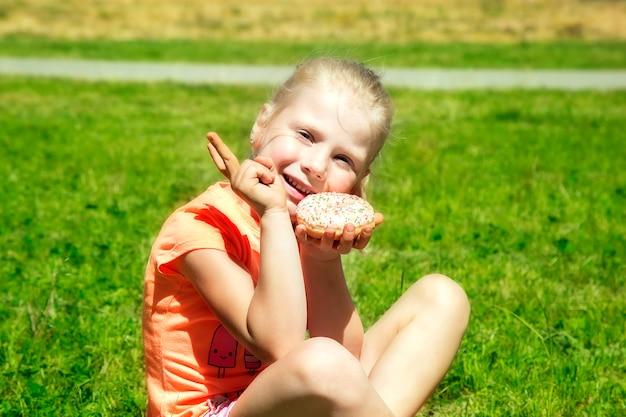 色のドーナツを持つ少女は緑の芝生に座っています。アウトドア