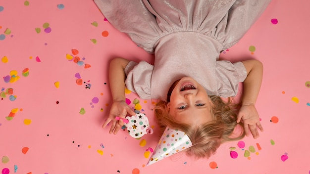 紙吹雪とパーティーハットを持つ少女