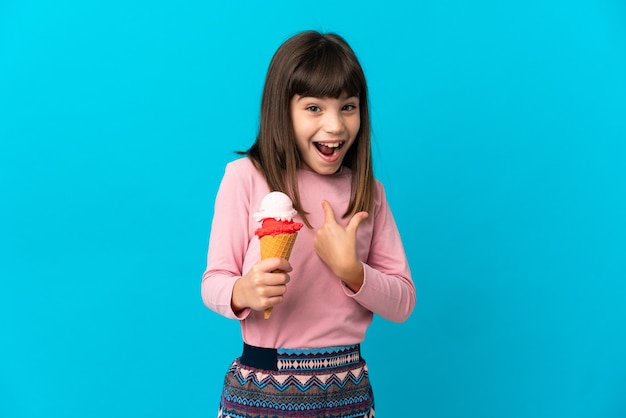 Little girl with a cornet ice cream isolated on blue wall with surprise facial expression