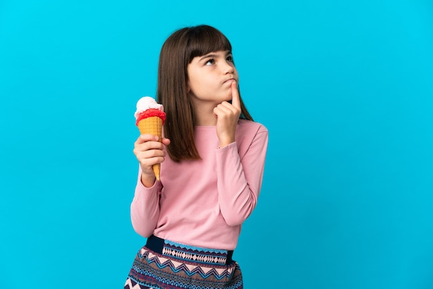 Little girl with a cornet ice cream isolated having doubts while looking up