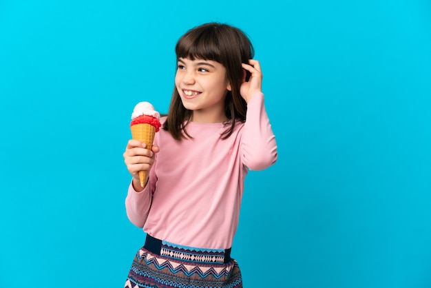 Little girl with a cornet ice cream isolated having doubts