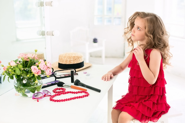 A little girl with cosmetics sitting near the mirror.