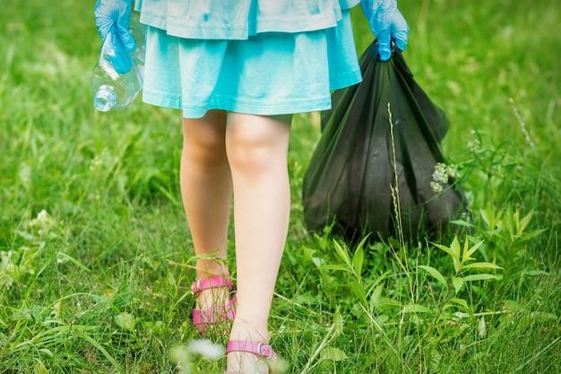 Маленькая девочка с мятой пластиковой бутылкой и мешком для мусора в руках, убирая мусор в парке