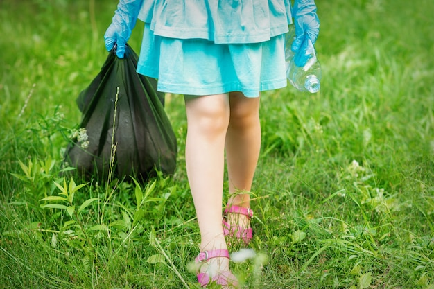 Little girl with crumpled plastic bottle and garbage bag in her hands while cleaning garbage in the park