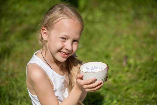 自然に牛乳のカップを持つ少女