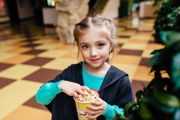 Маленькая девочка с чашкой попкорна в парке