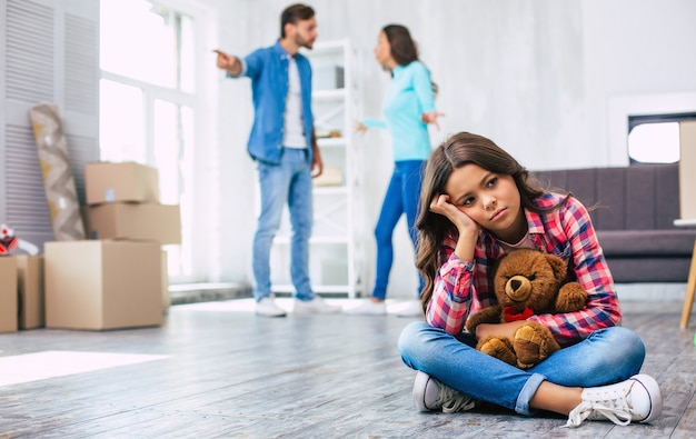 Little girl with curly chestnut hair is sitting on the floor, hugging a teddy bear, looking disturbed with her parents quarrelling on the background. house moving concept