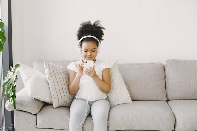 곱슬 머리를 가진 어린 소녀입니다. 어린이는 헤드폰에서 음악을 건조시킵니다. 집에서 즐겁게 지내십시오.
