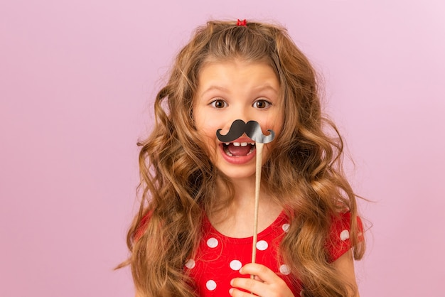 A little girl with curly hair holds a fancy paper moustache.