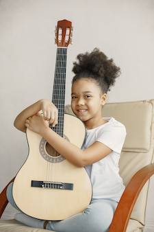 Little girl with curly hair. learning to play guitar. little girl in a chair.