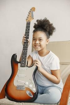 巻き毛の少女。ギターを弾くことを学ぶ。椅子に座っている少女。