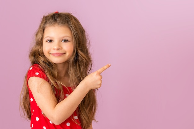 A little girl with curly hair points her finger to the side. copy space.