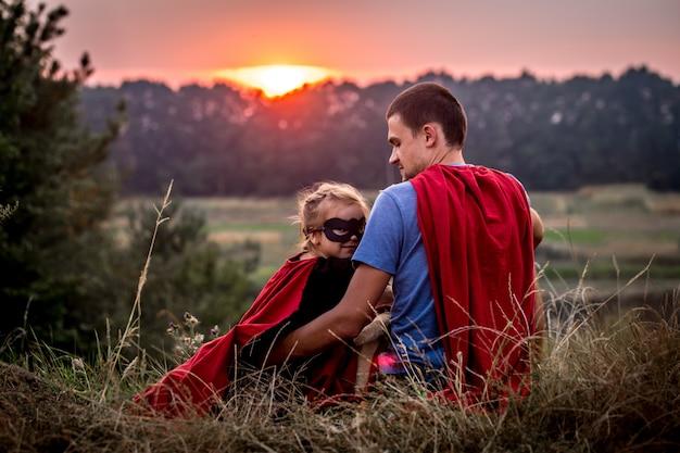 スーパーヒーロー、幸せな愛情のある家族に身を包んだお父さんを持つ少女