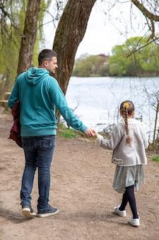 Маленькая девочка с папой в парке ранней весной в прохладную погоду, вид со спины.
