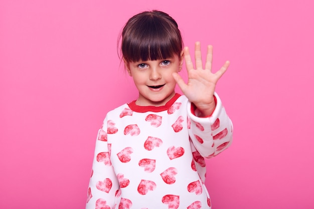 Little girl with dark hair, showing palm to camera, shows ban gesture, prohibits doing something, has confident expression, isolated over pink wall