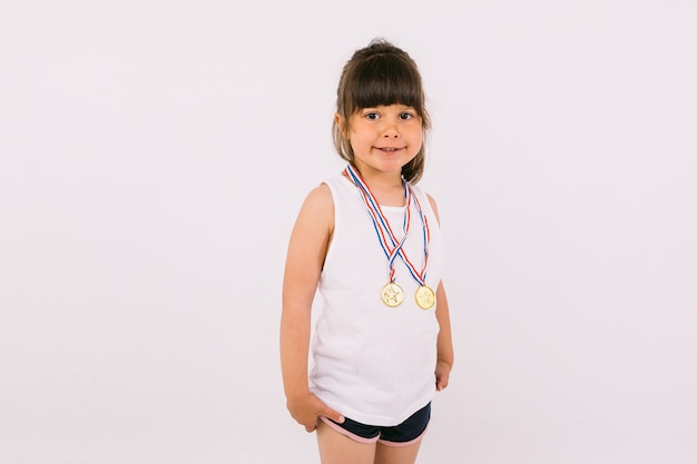 스포츠 챔피언 메달과 함께 검은 머리를 가진 어린 소녀. 스포츠와 승리 개념