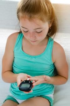 Маленькая девочка с диабетом, измерения уровня глюкозы в крови дома Premium Фотографии