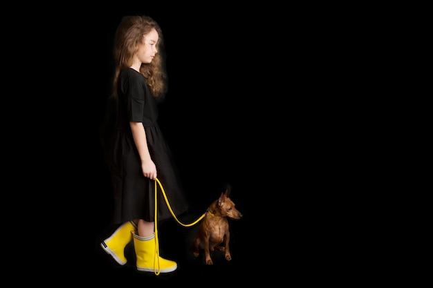 犬、黒と黄色の服を着た少女。黒の背景。スタジオ撮影。赤ちゃんペットのコンセプト。幸せな子供時代。高品質の写真