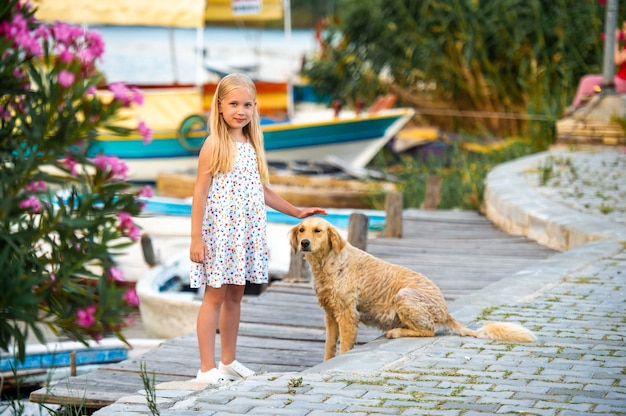 A little girl with a dog on the embankment by the river in a white sundress in the city of dalyan. turkey.